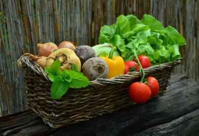 red tomato besides green vegetable leaf on brown basket